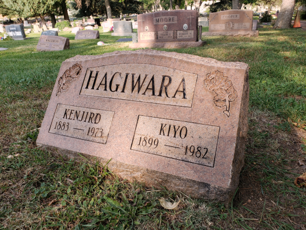 "Beautiful wide couple's gravemarker, that seems to be made out of local granite. It reads: ""HAGIWARA"". Carved roses border the name on each side. Under: ""KENJIRO, 1883–1973"", and ""KIYO, 1899–1982"". Other family markers, made of the same red granite, sit in the background. Moore, Cooper, Waldron, Sisk…"