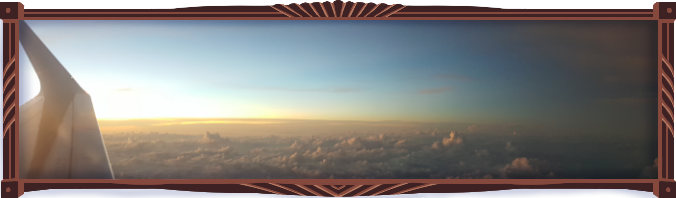 Photograph of the sunlight disappearing over a table of roughened clouds. The plane wing is visible to the left side. Away from the sun, the earth seems darkened by night already…