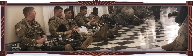 National Guard soldiers sit in a brightly lit White House hallway eating snacks and drinking plastic bottled water as they wait the rain out. They all look young. A couple of them are on their phones.