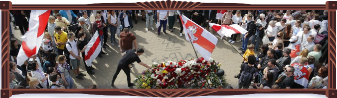 Photograph of the civic funeral of protester Alexander Taraikovsky. Hundreds of mourners wave old Belarusian white and red flags, and throw flowers onto the open casket. AP Photo/Dmitri Lovetsky.