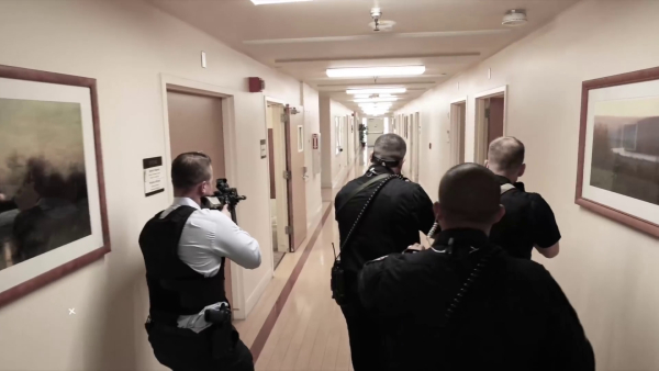 A team of four police officers enter one of the hallways. One of them is wielding a rifle.