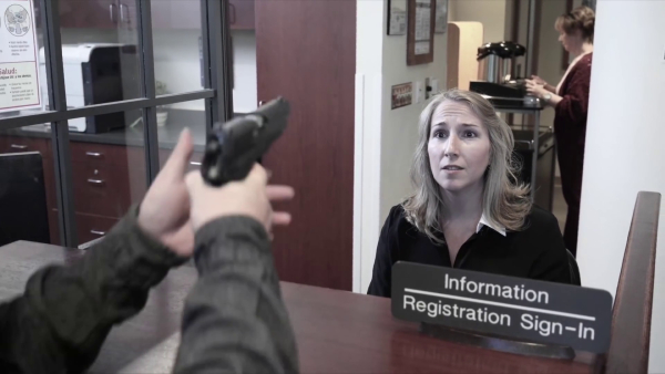 Flashback to the first receptionist who was killed. She can see the pistol clearly in the lone gunman's hands, the last image she sees before she dies.