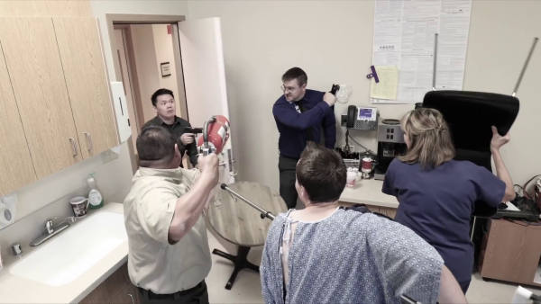 In a staff lounge, three workers and a patient prepare to ambush the gunman as he enters the room. They are wielding a fire extinguisher, a coffee pot, a chair, and an IV stand.