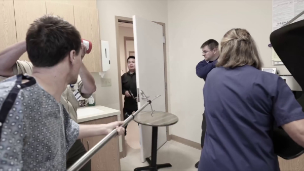 The lone gunman enters the staff lounge, opening the door and pushing the little end table that was propped up against it. Three workers and one patient armed with office furniture are waiting for him.