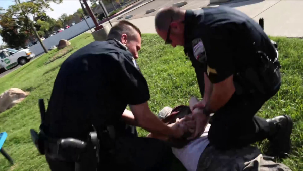 Twp cops tackle the confused guy to the ground and handcuff him.