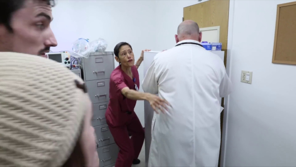 A hospital worker and a physician move to block the door of one of the offices with a large filing cabinet. The nurse instructs two visitors to silence their phones.