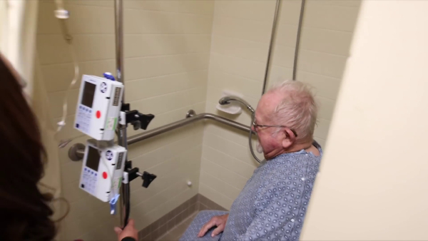 The nurse brings the IV stand into the shower stall.