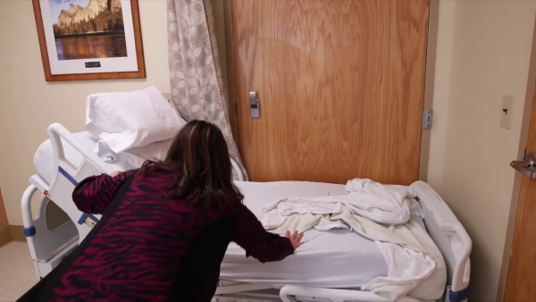 She pushes the bed up against the room entrance door.