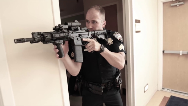 An officer enters a doorway with a rifle.