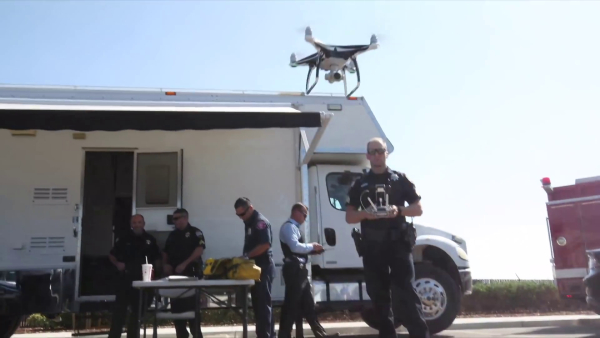 A team of police officers exit a van and prepare to enter the building. The officer in the foreground is piloting a drone.
