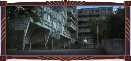 A dilapidated postwar Japanese apartment complex: a brutalist structure made out of concrete, now covered in black grime and moss, with trees outgrowing the planters. A lone schoolgirl walks outside the building. The sky is bright. It's eerie, but bright.