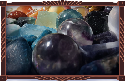 A bright assortment of tumbled, spherical, and obelisk stones, all sorted by color, arranged in a vintage Japanese porcelain bowl with gold floral trim and embellishments. Numerous specimens of fluorite with blue. Blue apatite, blue goldstone, a shining selenite sphere, blued aqua aura quartz. In the back, amazonite, red goldstone, carnelian, fire agate, mookaite jasper…