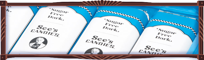 A sky blue box of the sky-blue wrapped sugar-free dark chocolate bars sold by See's Candies. Each candy bar has a photo of old Mary See.